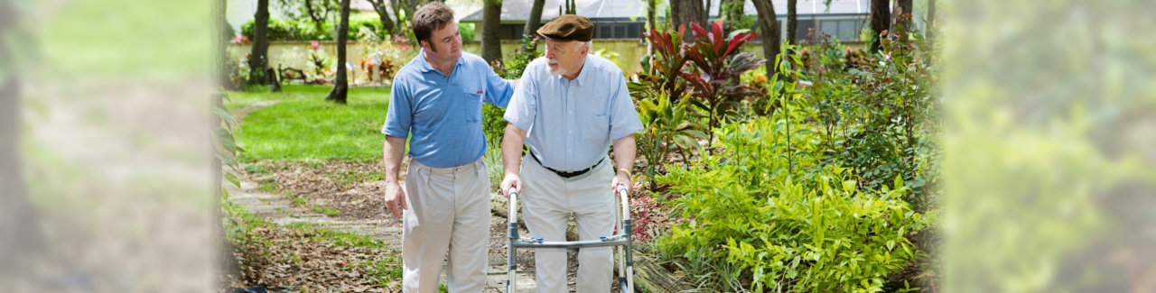 caregiver assisting an old man while walking